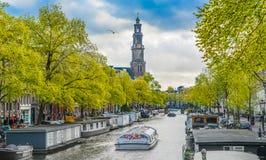 航行在通过Westertoren的Prinsengracht的一条运河船的游人 库存照片