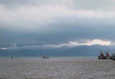 航行在风雨如磐的天空下的渔船 免版税库存图片