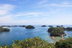 航行横跨小组的小船美丽的大海和清楚的天空的小岛小海岛 库存图片