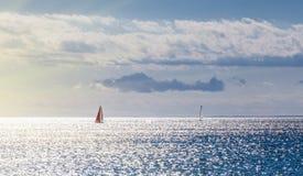 航行横跨落日的海洋的两条游艇发出光线 库存照片
