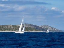 航行游艇在克罗地亚,在小船的有风夏天在岩石之间 库存照片