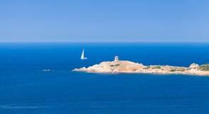 航行游艇在可西嘉岛的岩石海岸附近去 免版税库存照片