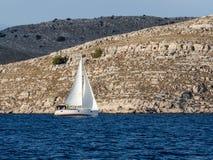 航行游艇在Croaatia,在小船的有风夏天在岩石之间 图库摄影