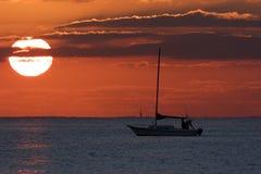 航行游艇现出轮廓反对日出 免版税库存照片