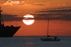 航行游艇现出轮廓反对日出 库存照片