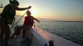 航行游艇的两名妇女,享受海远航,美好的日落,活跃休息 股票视频