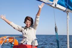 航行游艇的年长女子驾游艇者 免版税库存照片
