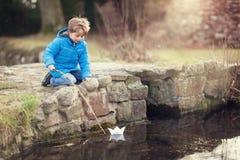 航行纸小船的男孩 免版税库存图片