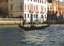 航行长平底船的平底船的船夫反对在大运河,威尼斯的威尼斯式样式大厦 免版税库存图片