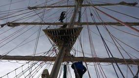 航行高船的成员f在黄昏攀登在后面光的帆柱进入围场和准备风帆 股票录像