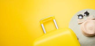舱内甲板在黄色背景放置有辅助部件的一个黄色手提箱放松的 旅行、休闲的概念 免版税库存照片