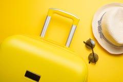 舱内甲板在黄色背景放置有辅助部件的一个黄色手提箱放松的 旅行、休闲的概念 库存照片
