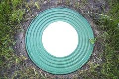 舱口盖很好与许多圆环的样式的生铁重的绿松石在绿草背景的  在白色的回合的中心 图库摄影