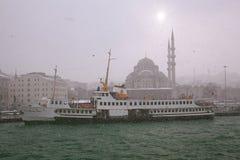 船和新的清真寺在伊斯坦布尔,斯诺伊天 库存照片