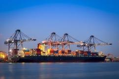 货船和起重机在口岸在河,暮色时间反射 免版税库存照片