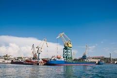 船和起重机在货物在塞瓦斯托波尔海湾端起 免版税库存图片