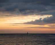 船在反对天空和云彩的海 免版税库存照片