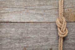 船在木纹理背景的绳索结 免版税库存图片