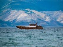 船在贝加尔湖中水域小山背景的  库存图片