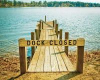 船坞在树包围的湖的被关闭的标志 库存图片