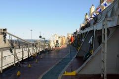 货船外部甲板,有安全齿轮的工作者 图库摄影