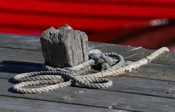 系船柱和红色渔船 库存照片