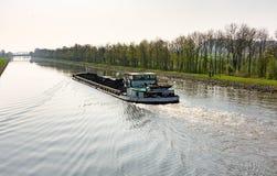 货船用煤炭装载了在运河在Wesermarsch 库存照片