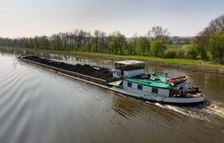 货船用煤炭装载了在运河在Wesermarsch 库存图片