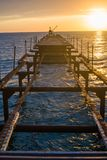 船的被拆卸的老码头在日落的海 库存图片