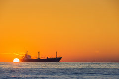 船航行在港口附近的海美好的日出的 图库摄影