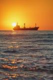 船航行在港口附近的海美好的日出的 免版税库存图片