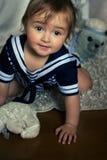 船舶镶边背心的微笑的女婴坐carpe 库存照片