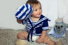 船舶镶边背心的微笑的女婴坐carpe 免版税库存照片