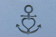 船锚和心脏被刻记入石表面 图库摄影