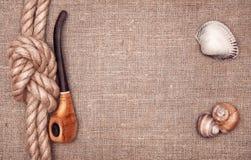 船绳索、贝壳和烟斗 免版税库存照片
