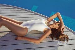 良好状态完善的棕褐色的皮肤的美丽的女孩在游泳池附近 免版税库存照片
