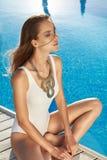 良好状态完善的棕褐色的皮肤的美丽的女孩在游泳池附近 库存图片