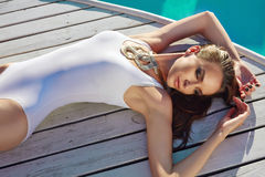良好状态完善的棕褐色的皮肤的美丽的女孩在游泳池附近 免版税库存图片