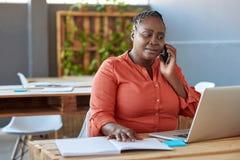 艰苦非洲女实业家在工作在一个现代办公室 库存照片