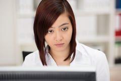 艰苦年轻亚裔女实业家在工作 免版税库存照片