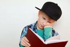 艰苦年轻男小学生照片在工作用他的手坐他的读书的面颊leraning新的材料为做准备 图库摄影