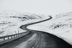 艰难路风景在冰岛的冬天 柏油路以斜向一边充分雪 库存照片