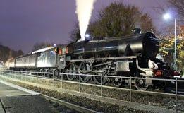 黑色五蒸汽火车在巴恩驻地的晚上 免版税库存照片