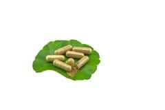 绿色亚洲Pennywort在白色的Centella asiatica和黄色药片胶囊 保存与裁减路线 免版税库存照片