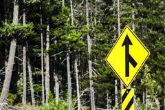 黄色交通合并标志有森林背景 库存图片