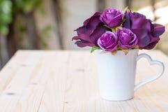 紫色人为在杯子心脏形状把柄上升了 免版税库存图片