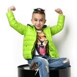 绿色冬天衣物夹克的时尚美丽的小男孩坐 库存图片