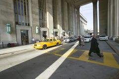 黄色出租车和走的商人外视图在第30个街道驻地,历史的Pl一个人口登记前面  图库摄影