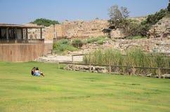 以色列- 7月30, -两青少年的女孩坐草在凯瑟里雅,以色列古老公园-凯瑟里雅2015年-凯瑟里雅2015年 免版税图库摄影
