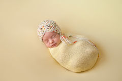 以黄色包扎的睡觉的新出生的女婴 免版税库存图片